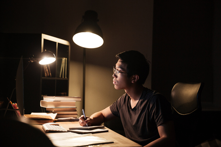 study: Concentrated asian young man in glasses using computer for studying and writing in notepad in the evening at home