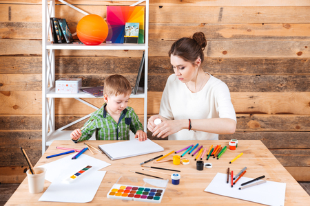 concetrated: Concentrated mother and little son sitting and drawing in art school