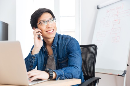 phone calls: Smiling asian young businessman with laptop talking on mobile phone in office