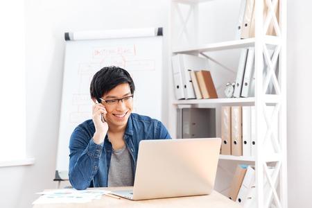 hablando por celular: apuesto joven empresario feliz en vidrios usando la computadora portátil y hablando por teléfono celular en la oficina