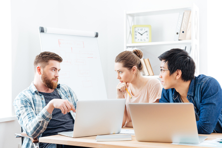 teamworking: Three serious young businesspeople having a business meeting in office Stock Photo