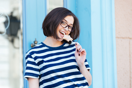 star shaped: Cheerful attractive young woman in glasses eating star shaped lollipop