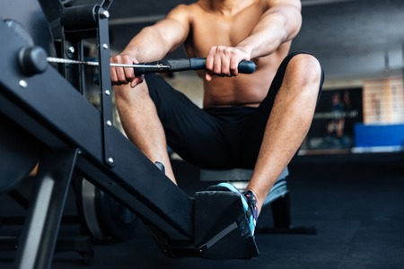 anaerobic: Cropped image of a fitness man using rowing machine in the gym