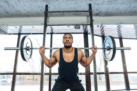 concetrated: Muscular weightlifter Doing squats Exercise using barbell in the gym Stock Photo
