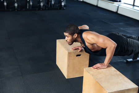musculine: Young Healthy Athlete Doing Push Ups As Part Of Bodybuilding Training at the gym