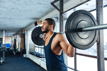 violence in sports: Muscular Fitness Man Doing Heavy Exercise in the gym using barbell Stock Photo