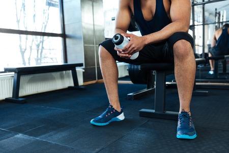 hombre deportista: Imagen recortada del hombre descansando con una botella de agua en el gimnasio