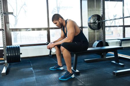 hombre deportista: Afro americano aptitud del hombre descansando en el banco en el gimnasio