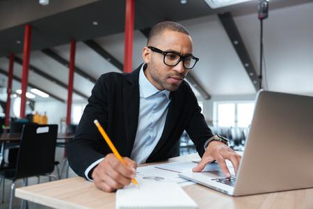 jornada de trabajo: empleado se concentr� joven que mira el monitor de la computadora y observando durante la jornada de trabajo en la oficina Foto de archivo