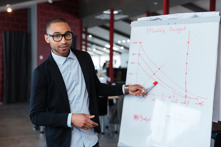 paper board: Businessman pointing and presenting something on the flipchart Stock Photo
