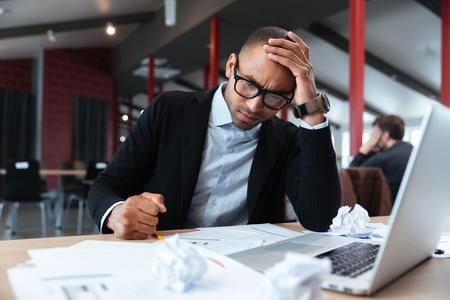 businessman thinking: Focused businessman thinking over laptop