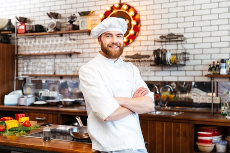 Smiling attractive chef cook with beard standing with hands folded on the kitchen