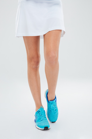 tennis skirt: Closeup portrait of a sexy female legs in skirt isolated on a white background Stock Photo