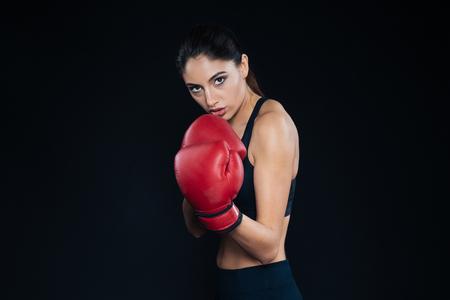 mujer deportista: boxeador de sexo femenino que presenta en fondo negro Foto de archivo