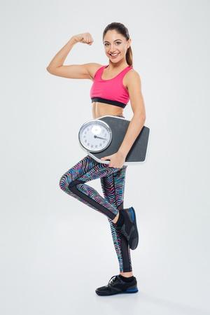cuerpo entero: Feliz fitness mujer que sostiene el éxito báscula aislado en un fondo blanco Foto de archivo