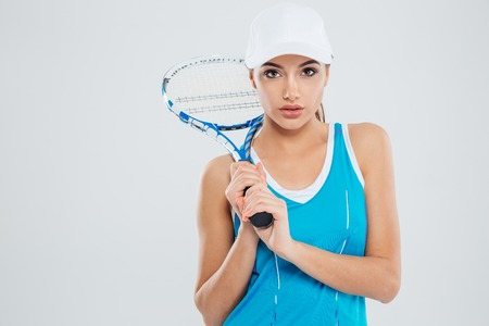 racquet: Portrait of a beautiful woman holding tennis racquet and looking at camera isolated on a white background Stock Photo