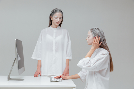 alien women: Two alien cosmic women using computer over gray background Stock Photo