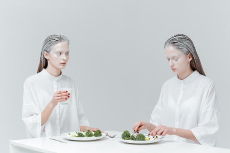 concept magical universe: Two beautiful pretty fashion girls eating at the table over gray background