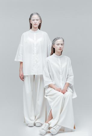 alien women: Two beautiful mystical alien women in white dress over gray background