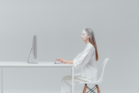 concept magical universe: Cosmic fashion woman sitting at the table with computer, pc over gray background