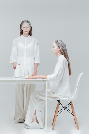 concept magical universe: Two beatiful unusual women having a meal at the table over gray background
