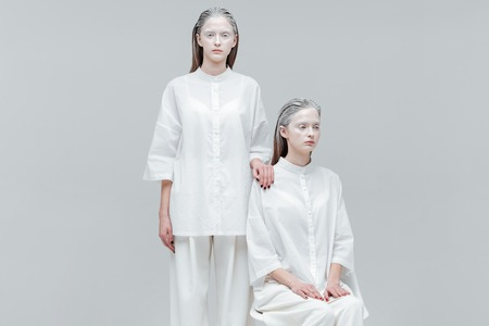 Dos hermosas mujeres en ropa de moda blancas sobre fondo gris
