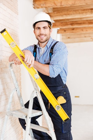housebuilding: Close-up portrait of a smiling worker standing on the ladder and holding construction yellow level inoors Stock Photo