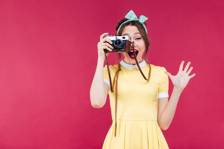 Happy pretty pinup girl in yellow dress taking pictures with vintage camera over pink background Stok Fotoğraf