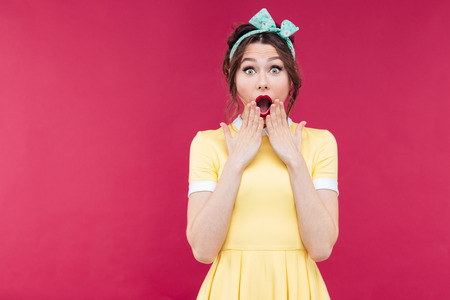 Portrait of wondered charming pinup girl in yellow dress with mouth opened over pink background