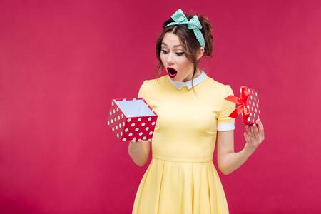 sorprendido: Preguntado cuadro joven linda regalo de la apertura de la mujer sobre el fondo de color rosa