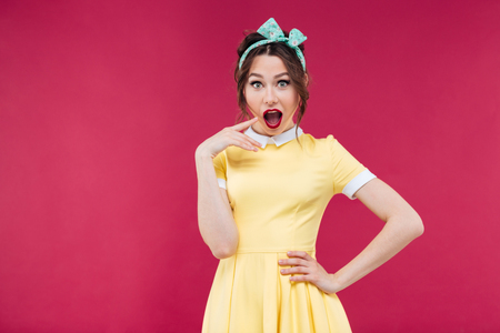 mouth opened: Surprised beautiful pinup girl in yellow dress standing with mouth opened over pink background