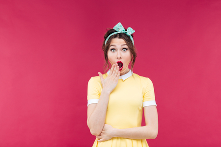 mouth opened: Amazed pretty pinup girl in yellow dress standing with mouth opened over pink background
