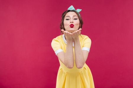 Happy pretty pinup girl in yellow dress sending a kiss over pink background Stock fotó
