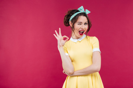 Cute playful pinup girl in yellow dress winking and showing ok sign over pink background