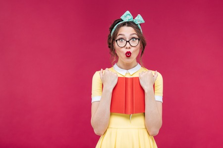 funny glasses: Charming surprised pinup girl in glasses standing and holding red book over pink background