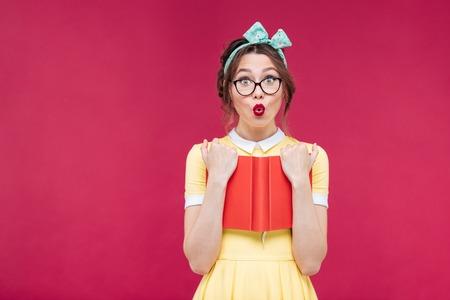 Urocze zaskoczony pinup dziewczyna w okularach stoi i trzyma czerwona książka na różowym tle