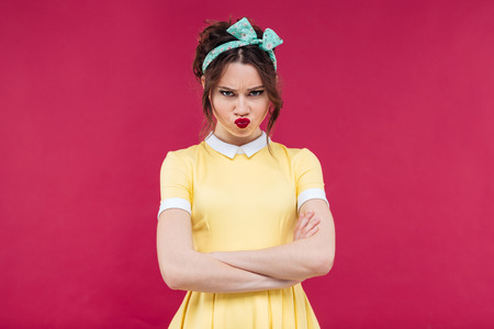 frowning: Sad frowning pinup girl in yellow dress standing with arms crossed over pink background