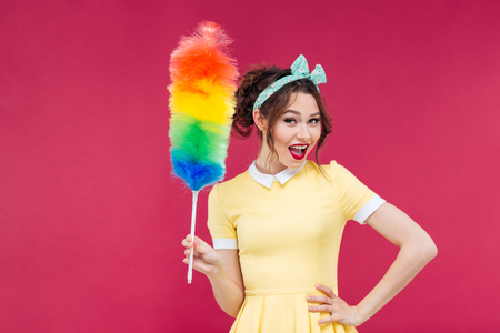 bright housekeeping: Smiling attractive pinup girl holding colorful duster brush over pink background