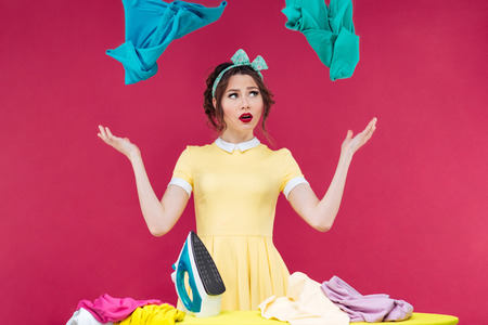houseclean: Pretty upset young woman with iron throwing clothes in the air over pink background