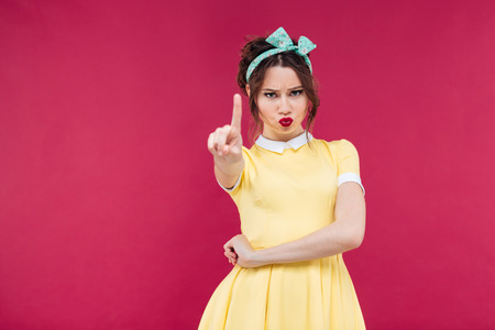 strict: Serious strict young woman in yellow dress showing warning sign over pink background