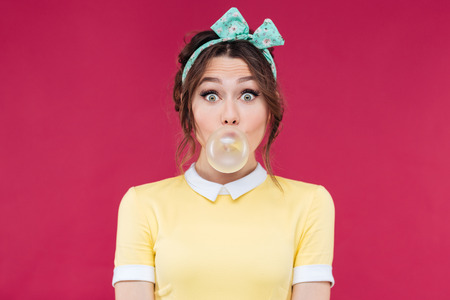 Amazed cute pinup girl in yellow dress blowing a bubble gum balloon over pink background 写真素材