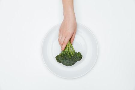 tomando refresco: Top view of woman hand putting broccoli on the plate over white background