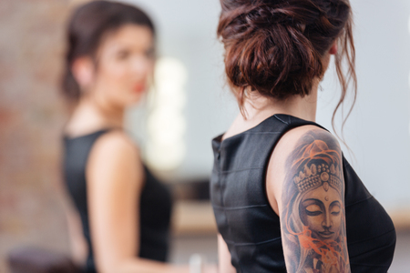 Back view of pretty young woman in black dress with tattoo on her hand standing in front of the mirror Фото со стока
