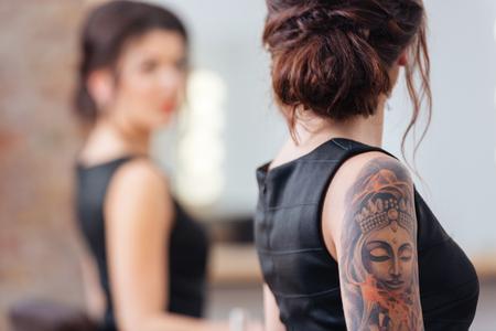 tatouage sexy: Vue arrière de la jolie jeune femme en robe noire avec un tatouage sur sa main, debout devant le miroir Banque d'images