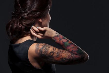 Punto di vista posteriore della bella giovane donna con la mano tatuata