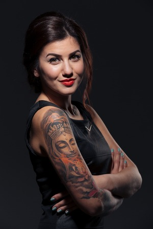 Portrait of attractive smiling young woman with tattoo on her hands