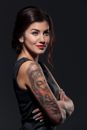 tattoed: Beautiful tattoed young woman standing with hands folded Stock Photo