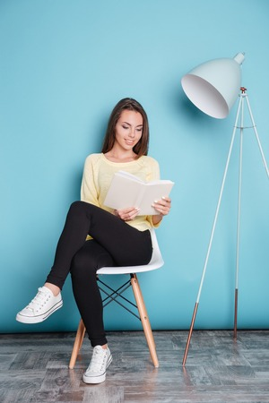 Beautiful smart young woman reading book and sitting on the chair isolated on the blue background Foto de archivo