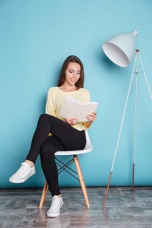 Mooie slimme jonge vrouw leesboek en zitten op de stoel geïsoleerd op de blauwe achtergrond Stockfoto