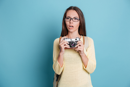 photocamera: Pensive beautiful girl with photocamera isolated on the blue background